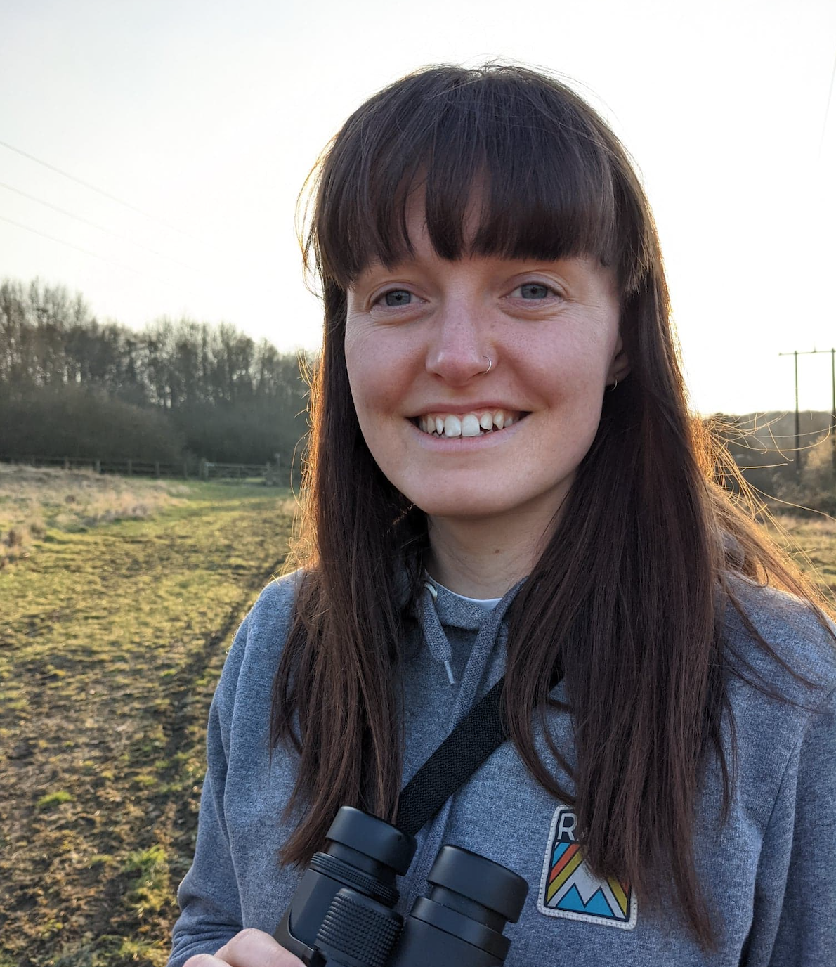 Jasmine smiling at the camera holding binoculars and standing in a sunny field.
