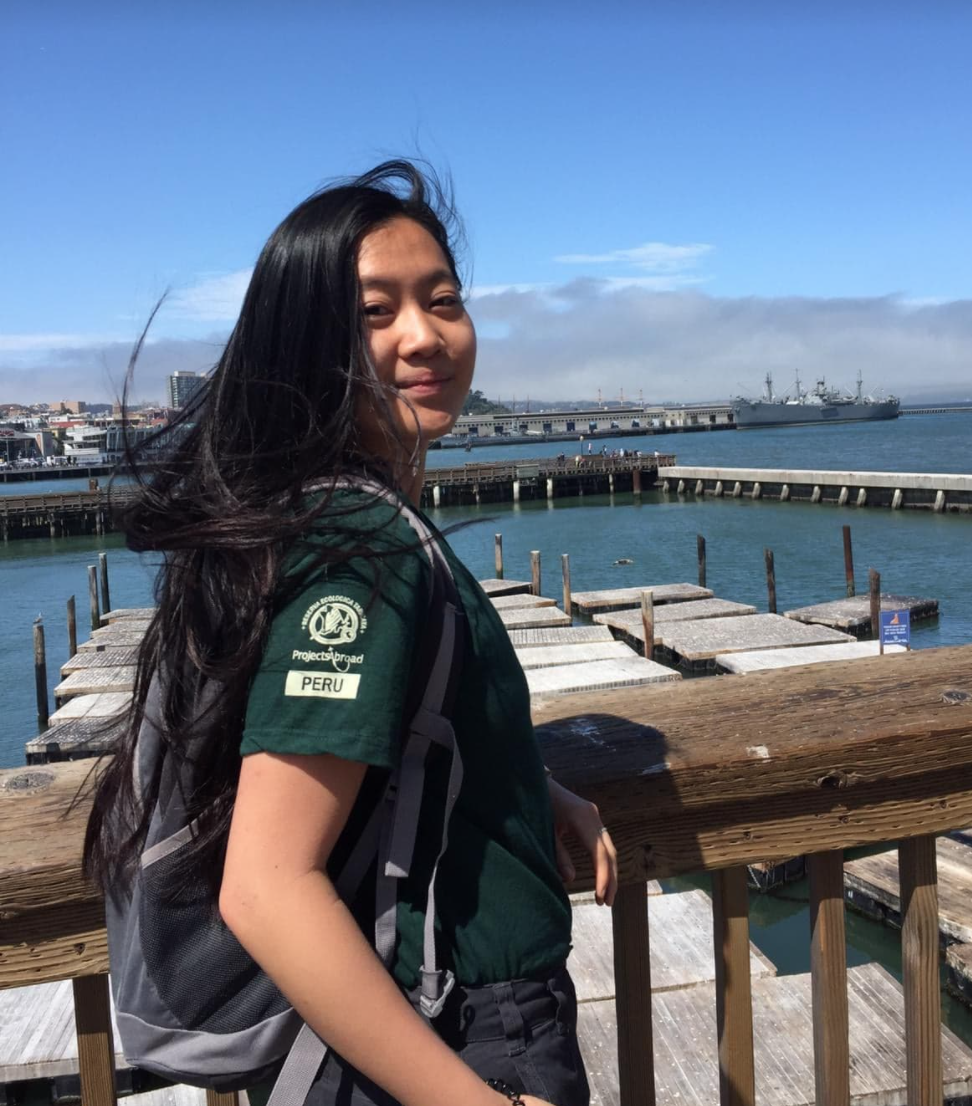 Rebecca standing on a pier with a rucksack and green t shirt, her head turned towards the camera and smiling.